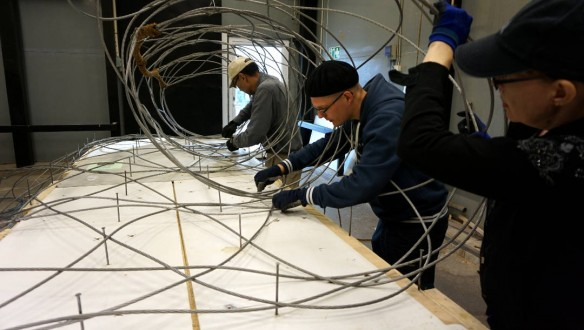 people working on large wire lace